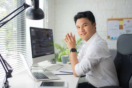 Handsome young Asian businessman trading stocks on the laptop screen on his desk. Data analysis concept. Stock fotó