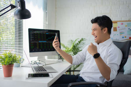 Young Asian businessman in casual wears excited, shouting, and a joyful expression in the office as he looks at trading charts on his smartphone. Stock fotó