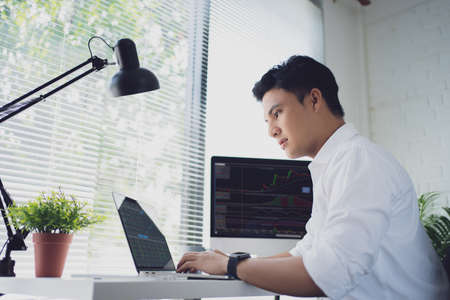 Young Asian man trades stocks on his laptop screen on his desk. He is serious about trading stocks. Stock fotó