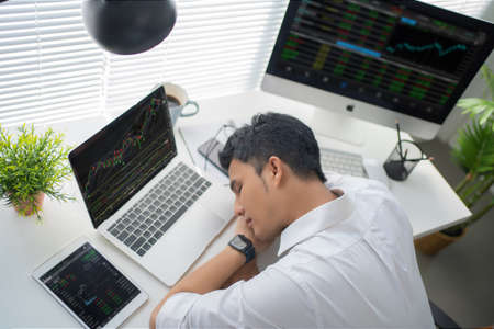 Young businessman tired of sleeping on the desk while working in a modern office. Stock fotó