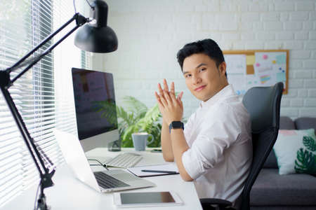 Asian businessman handsome happy and smiling with a laptop while sitting in the workspace.