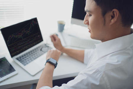 Young man trades stocks on a laptop screen on desk. He was looking at the watch on his wrist. Stock fotó