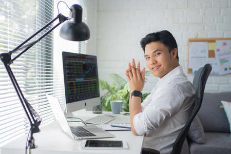 Asian businessman handsome happy and smiling at the camera while sitting in a modern office.