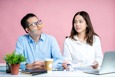 Young woman is upset when her co-workers are stupid. He doesn't comment and doesn't work together. Isolated on a pink background