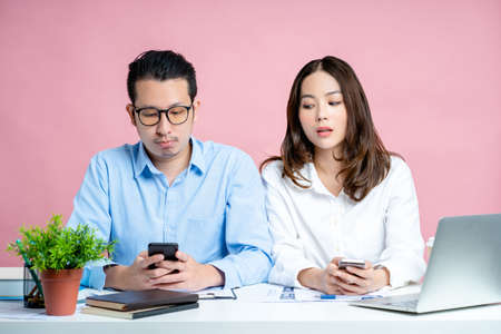 Portrait of young office worker using the internet on a smartphone on a desk on a pink background. She peeked at her boyfriend's smartphone, Isolated background.