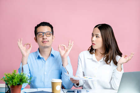 Beautiful woman is dissatisfied with the actions of her colleague on the desk on a pastel pink background. Stock fotó