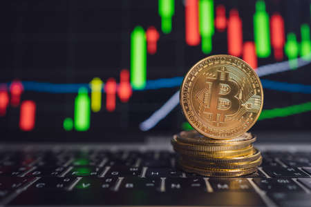 Nakhon Pathom, Thailand - 27 April 2021: Close up of Bitcoin stack with graphs the rise and fall of cryptocurrencies. Stock fotó