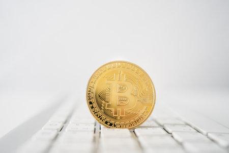 Golden bitcoin coin on laptop computer keyboard.