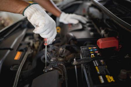 Young car mechanic repairing the car with a screwdriver. Banco de Imagens
