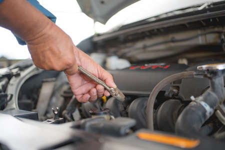 Maintenance concept. A close-up of a young auto mechanic repairing a car with a wrench.