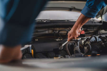 Hand of the auto mechanic was repairing the problem car, he held a wrench. Banco de Imagens