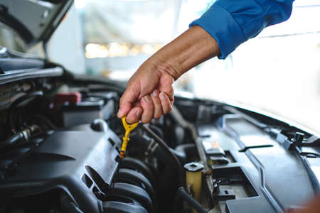 Mechanic to check the oil level. Car service and maintenance concept.