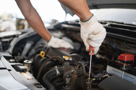 Hand of an auto mechanic is repairing the problematic car. He was wearing white cloth gloves, holding a screwdriver. Banco de Imagens