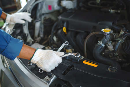 Close up hands of auto mechanic doing car service and maintenance. Banco de Imagens