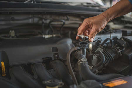 Auto car repair service center. Mechanic checks the water level of the radiator in the car.