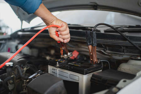 Auto mechanic is charging the battery. Auto repair service center.