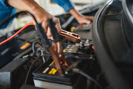 Auto mechanic is charging the battery. He works in a garage. Car repair service and car problems concept.