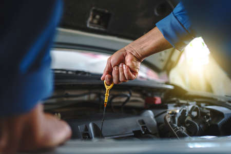 Close up of the hand of an asian mechanic. Auto mechanic is checking the engine oil in a vehicle at the garage. Maintenance concept.