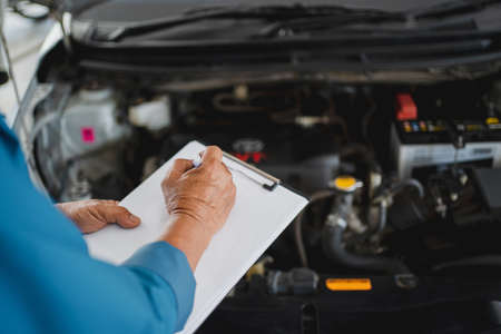 Mechanic holding a clipboard of service order working in garage. Repair service. Banco de Imagens
