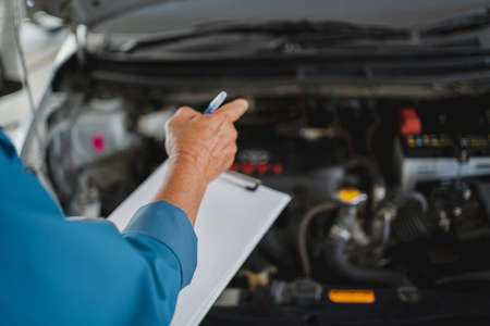 Auto mechanic holds the clipboard of service orders working in the garage. Car service and maintenance concept.
