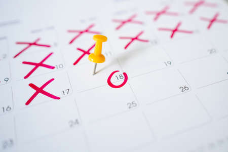 Calendar with a red pin on the 18th, mark the date of the event with a pin.