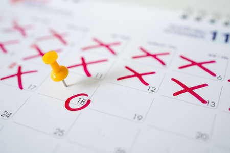 Calendar with yellow pins on the 18th. Yellow pins are the dates of the calendar or planner.