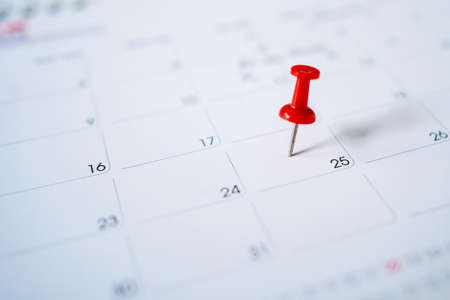 Selective focus. Photo picture of a calendar with a red pin on the 25th.