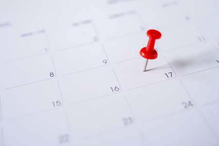 Selective focus. Picture of red pin embroidered on June 17 in the calendar. Banco de Imagens
