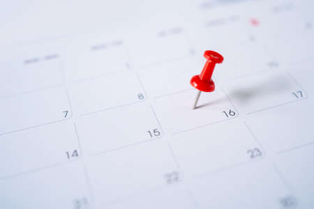 Selective focus. Picture of red pin embroidered on June 16 in the calendar. Concept of to do planning.