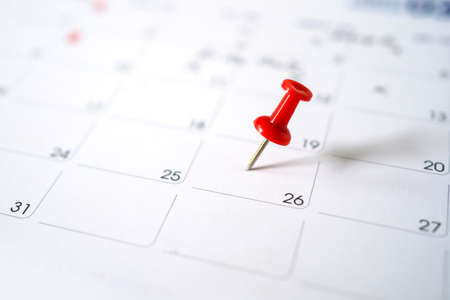 Closeup red pin on the calendar. Calendar with red pins on the 20th, mark the date of the event with a pin. Banco de Imagens