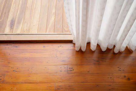 White curtains on the windows and the wooden floor in the room at home. Banco de Imagens