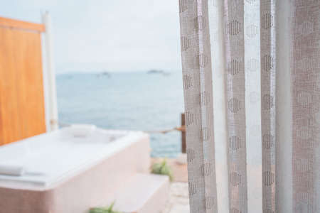 Close-up photo of white curtains and sea view background.