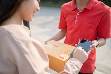 A smiling Asian woman receiving a package from a delivery man at home. Banco de Imagens