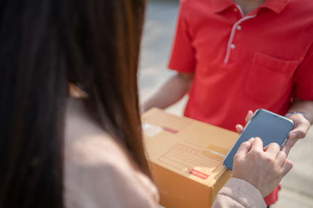 Young woman is writing a signature on a digital phone after receiving a parcel from delivery man. Banco de Imagens
