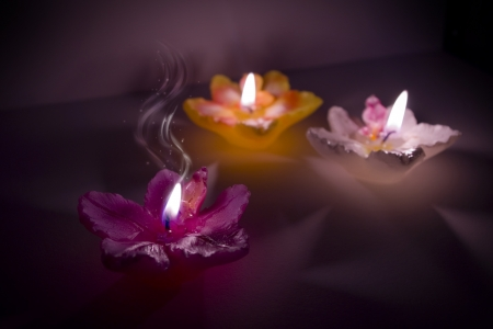 Three flower shape candles with magic smoke Stock Photo - 17775854