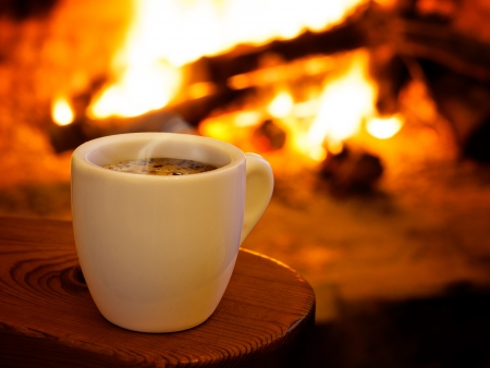warm drink: A cup of hot coffee in front of fireplace Stock Photo