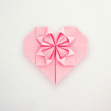 A pink paper origami heart on white canvas back Stock Photo