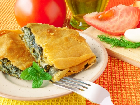 Two pieces of spinach pie on the plate with tomato, garlic and olive oil on back