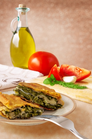 Two pieces of spinach pie on a plate with olive oil and tomatoes on back