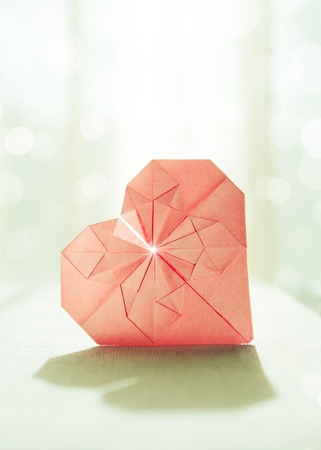 Stylized image of the pink origami paper heart with back light