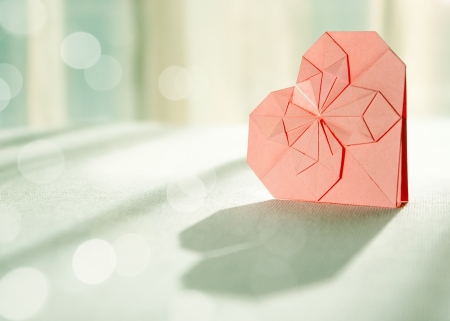 Stylized image of the pink origami paper heart with back light and bokeh effect Stock Photo