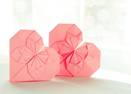 Horizontal image of two sunlit pink origami paper hearts