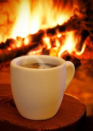 A cup of hot coffee with a fireplace on the back
