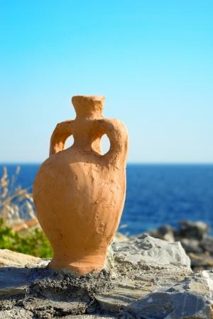 A hanmade decorative greek amphora over the blue sea and sky