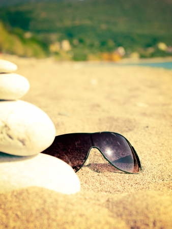 Sea, sandy beach and sunglasses with reflection of the sun