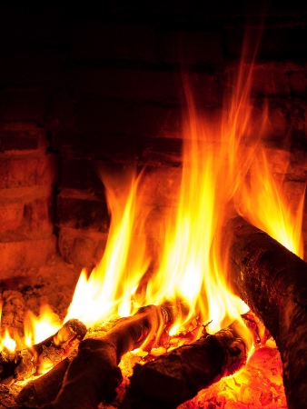 Bright warm fire in fireplace vertical image Stock Photo