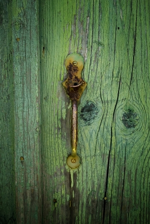 A grunge old wooden weathered door with rusty metal handle