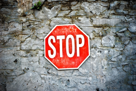 Grunge red stop sign on a stone wall Stock Photo