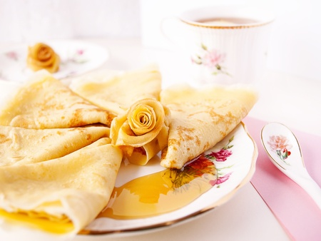 A composition of Russian traditional homemade pancakes served with honey and a cup of tea on back