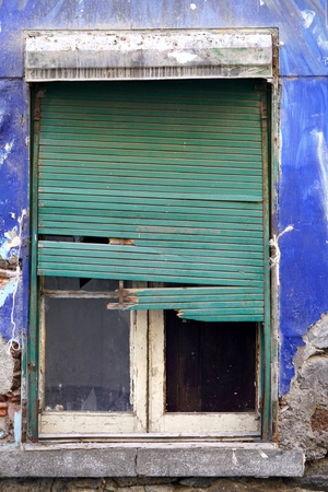 morbid: blue colored old home with a morbid green rolling shutter